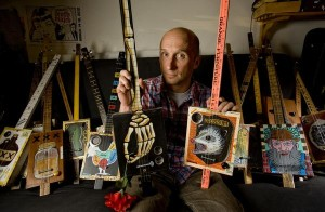 Jason Farthing with some of his custom cigar box guitars that he has been making in his Aliso Viejo garage since 2007.